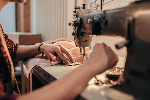 Tailor working with sewing machine.